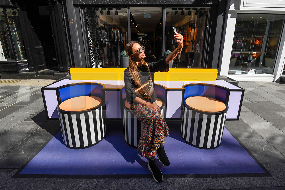 """© Licensed to London News Pictures. 14/09/2019. LONDON, UK.  A tourist takes a selfie on a sculptural bench as """"Walala Lounge"""" opens in Mayfair's South Molton Street.  Artist and designer Camille Walala's installation comprises 10 sculptural benches, accompanied by planters and a series of oversized flags strung, bunting-style, from shopfront to shopfront, converting the street into an immersive corridor of colour as part of this year's London Design Festival.  Photo credit: Stephen Chung/LNP"""