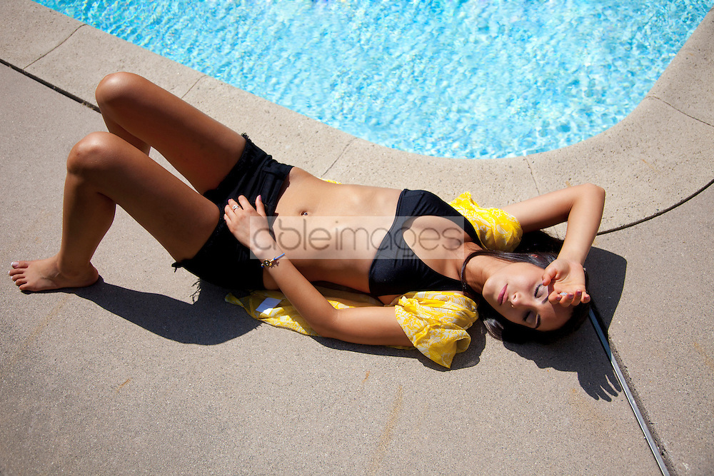 Woman Sunbathing on the Edge of Swimming Pool, High Angle View