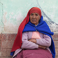 An elderly woman watching a political campaign gathering in a street of Santa Maria de Chicmo district.