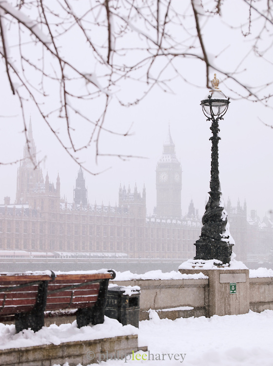 The south bank of the River Thames covered in snow opposite the Houses of Parliament and Big Ben, London, UK