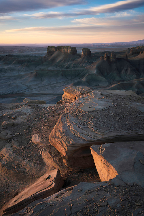 The first light of sunrise strikes the rock walls and illuminates the rocky outcrops over a martian looking landscape in Southern Utah.