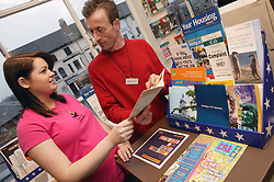 Single parent looking through information leaflets in a public library,