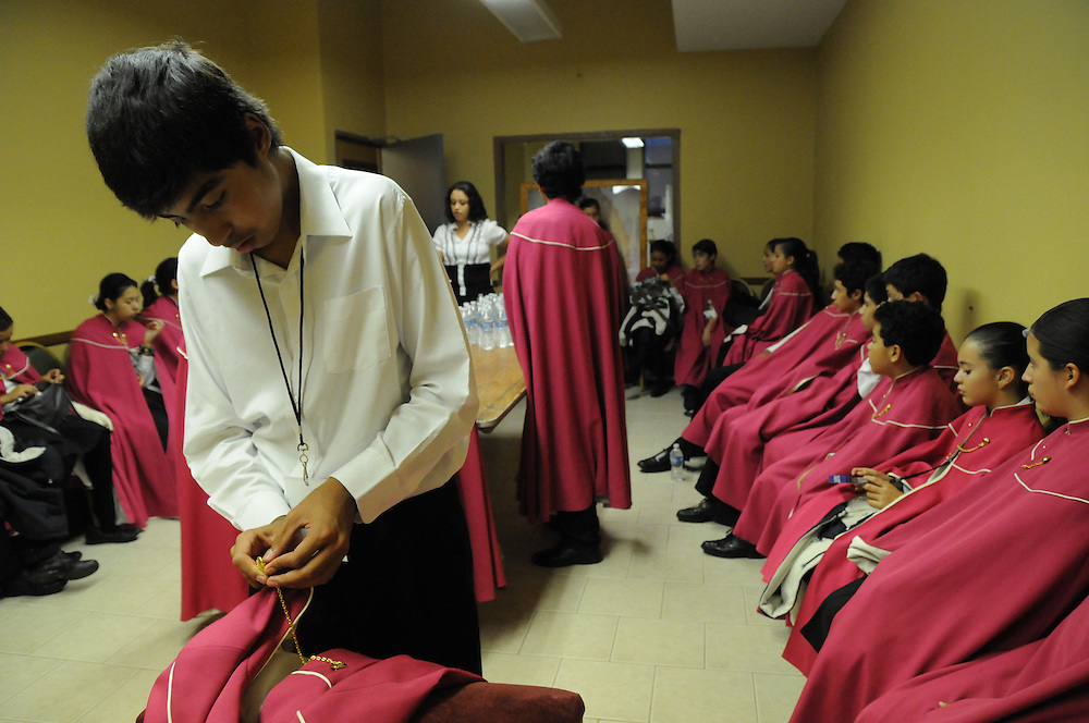 Edson Jose Villa Pañazoa, 13, checks a decorative button on his cape before a choral performance with Niños Cantores de Morelia before a packed audience at St. Gall Parish on Chicago's southwest side.