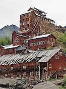"""Kennecott Concentration Mill rises 14 stories tall beneath Bonanza Ridge in the Wrangell Mountains, Alaska, USA. Kennecott Mines National Historic Landmark and nearby McCarthy lie within Wrangell-St. Elias National Park and Preserve, the largest National Park in the USA. Old mine buildings, artifacts, and colorful history attract summer visitors. Remote McCarthy is connected to Chitina via the McCarthy Road spur of the Edgerton Highway. At the east end of McCarthy Road, visitors must park their vehicle and walk across the footbridge to McCarthy. From McCarthy, a privately-operated shuttle takes visitors 5 miles to Kennecott. After copper was discovered between the Kennicott Glacier and McCarthy Creek in 1900, the Kennecott town, mines, and Kennecott Mining Company were created and named after the adjacent glacier. Kennicott Glacier and River had previously been named after Robert Kennicott, a naturalist who explored in Alaska in the mid-1800s. The corporation and town stuck with a mistaken spelling of """"Kennecott"""" with an e (instead of """"Kennicott"""" with an i). Partly because alcoholic beverages and prostitution were forbidden in the company town of Kennecott, the neighboring town of McCarthy grew quickly to provide a bar, brothel, gymnasium, hospital, and school. The Copper River and Northwestern Railway reached McCarthy in 1911 to haul over 200 million dollars worth of ore 196 miles to the port of Cordova on Prince William Sound. By 1938, the worlds richest concentration of copper ore was mostly gone, the town was mostly abandoned, and railroad service ended. Not until the 1970s did the area began to draw young people for adventure and the big money of the Trans Alaska Pipeline project. Declaration of Wrangell-St. Elias National Park in 1980 drew adventurous tourists who helped revive McCarthy with demand for needed services. Wrangell-St. Elias National Park and Preserve is honored by UNESCO as part of an International Biosphere Reserve and UNESCO World Heritage"""