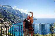 Selfie. A young couple capture am moment in Positano, the main town on the Amalfi Coast. Stretching about 30 miles or 50km along the southern side of the Sorrentine Peninsula, most famous for the town of Sorrento, the Amalfi Coast (Costiera Amalfitana) is one of Europe's most breathtaking. Cliffs terraced with scented lemon groves sheer down into sparkling seas; whitewashed and pastel colored villas cling precariously to unforgiving slopes while sea and sky merge in one vast blue horizon.