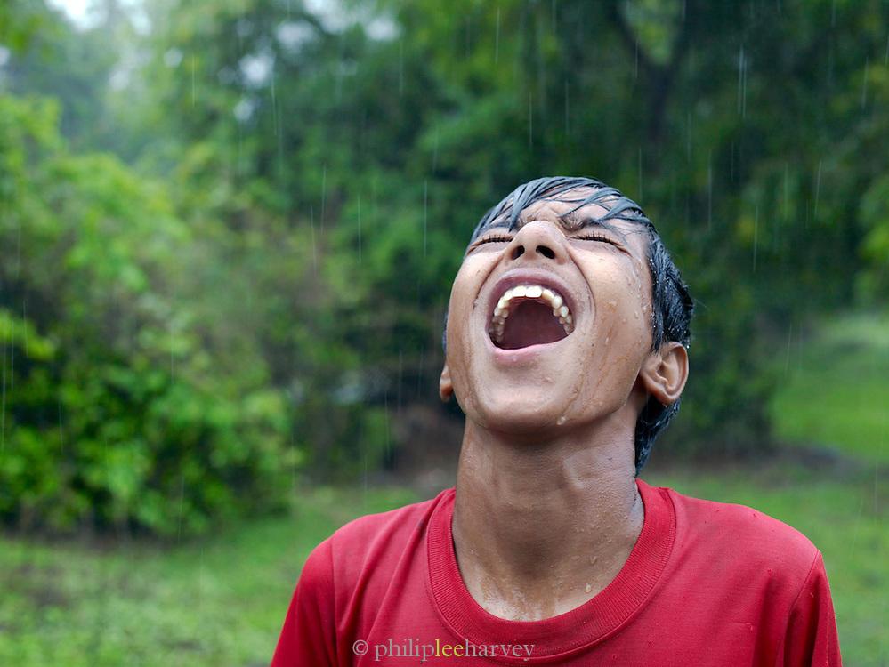 Local boy enjoys the onset of monsoon rains, Goa, India