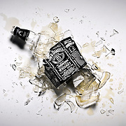 A smashed Jack Daniels bottle, glass and whiskey on the floor with the iconic brand label still clearly visible.