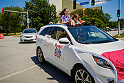 """24 JULY 2020 - DES MOINES, IOWA: Girls stand in the sun roof of their family car during a teachers' motorcade around the Iowa State Capitol. Hundreds of teachers from across Iowa came to the state capitol Friday to protest Governor Kim Reynolds' order that school must reopen with in person education and minimized the potential for """"distance learning."""" The event was one of the largest COVID-19 protests in Iowa since the pandemic started, more than 740 teachers signed up to attend the protest. After the protest officially ended, many teachers left the capitol and drove to Gov. Reynolds' residence, where they drove around her mansion and honked horns. Some people left notes on the entrance to the governor's residence. Gov. Reynolds ordered the school reopening last week, but according to teachers, the state has not implemented health guidelines or bought protective equipment like face masks in the quantity required to slow the spread of the Coronavirus (SARS-CoV-2). Iowa's numbers of COVID-19 infections are up statewide.          PHOTO BY JACK KURTZ"""