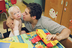 Father with young son playing in hospital playroom,