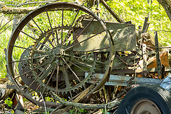 Old pieces of rusty machinery that have been discarded in the light wooded area along a creek in Central Illinois