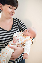 Mother holding her newborn baby in her arms, smiling