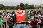 """A speaker draped in the Afghani national flag as people take part in a demonstration in front the Reichstag  building, seat of the German lower house of Parliament, the Bundestag in Berlin, Germany, August 17, 2021. About 1000 people gathered in front of the  under the call """"Airlift now! Create safe escape routes from Afghanistan!"""", the spontaneous event was organized by Seebrücke and several other human-rights organizations."""