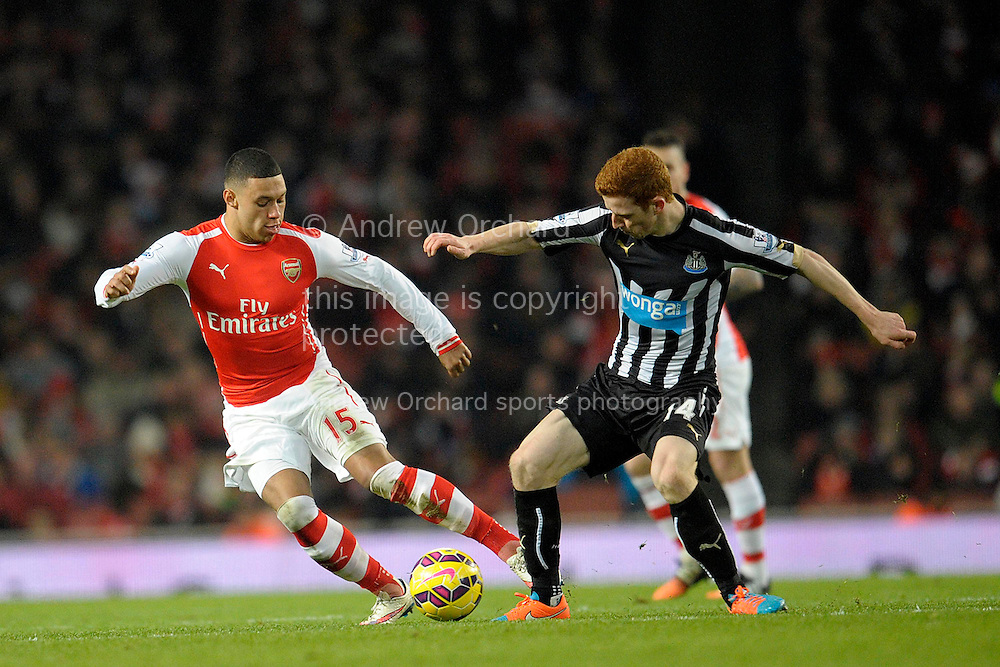 Jack Colback of Newcastle United challenges Alex Oxlade-Chamberlain of Arsenal. Barclays Premier league match, Arsenal v Newcastle Utd at the Emirates Stadium in London on Saturday 13th December 2014.<br /> pic by John Patrick Fletcher, Andrew Orchard sports photography.
