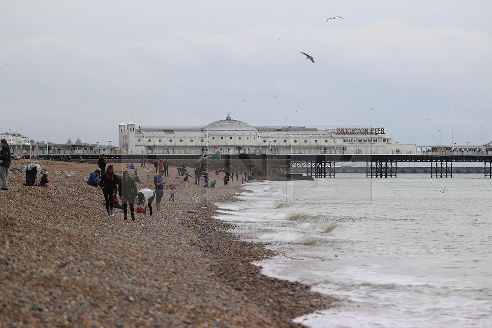 © Licensed to London News Pictures. 21/10/2014. Brighton, UK. Grey skies with temperatures reaching 14C in Brighton and the South Coast. Only a handful of people relaxing on the beach. Photo credit : Hugo Michiels/LNP