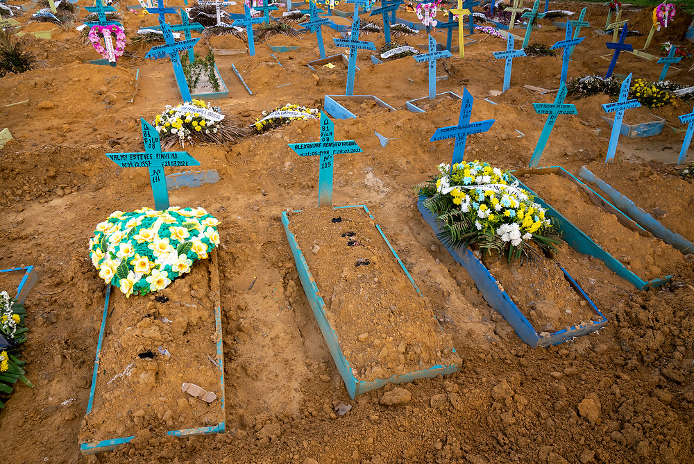 """Blue grave markers called """"Castilhos"""" are laid out at Nossa Senhora Aparecida public cemetery for people who died of Covid March 30, 2021 in Manaus, Brazil. Brazilian residences are receiving the CoronaVac vaccine, also known as the Sinovac COVID-19 vaccine. CoronaVac is an inactivated virus COVID-19 vaccine developed by the Chinese company Sinovac Biotech and has been in Brazil's Phase III clinical trials. Photo Ken Cedeno"""