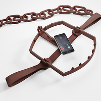 Distractions from mobile devices are impacting your capacity to focus on your work. iPhone with an incoming call on the trigger of a bear trap.
