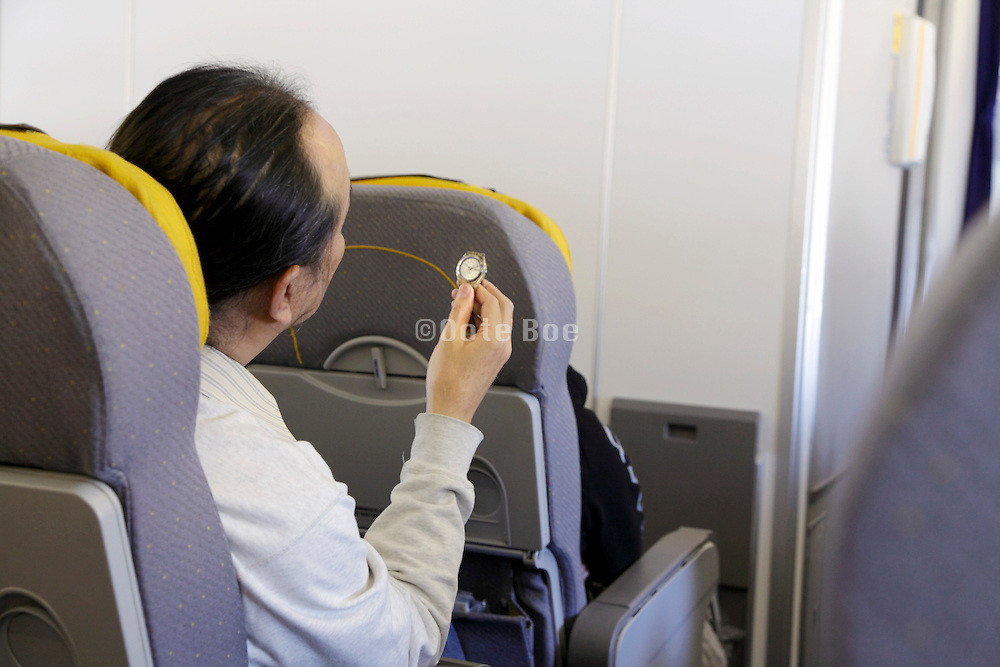 airplane passenger comparing his watch time against the arrival time during flight