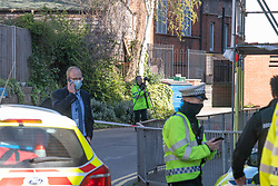 © Licensed to London News Pictures. 22/04/2021. Walton-on-Thames, UK. A police photographer in an alley way next to an M&S store. Police responded to an incident at 14:15 BST on church Street in Walton-on-Thames, police and forensic investigators could be seen at he scene. Photo credit: Peter Manning/LNP