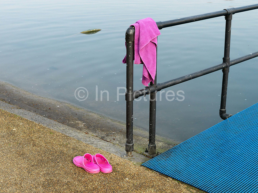 A pink towel and a pair of flip flops belonging to a member of the Serpentine Swimming Club, Hyde Park, London, UK. The Serpentine Lake is situated in Hyde Park, London's largest central open space. The Serpentine Swimming Club was formed in 1864 'to promote the healthful habit of bathing in open water throughout the year'.  Its headquarters were beneath an old elm tree on the south side of the lake, a wooden bench for clothing being the only facility.  At this time London was undergoing rapid expansion and Hyde Park was now in the centre of a densely populated built up area and provided a place of relaxation to its urbanised masses. Now, the club has its own (somewhat spartan) changing facilities and members are  permitted by the Royal Parks to swim in the lake any morning before 09:30.  They race every Saturday morning throughout the year, regardless of the weather.