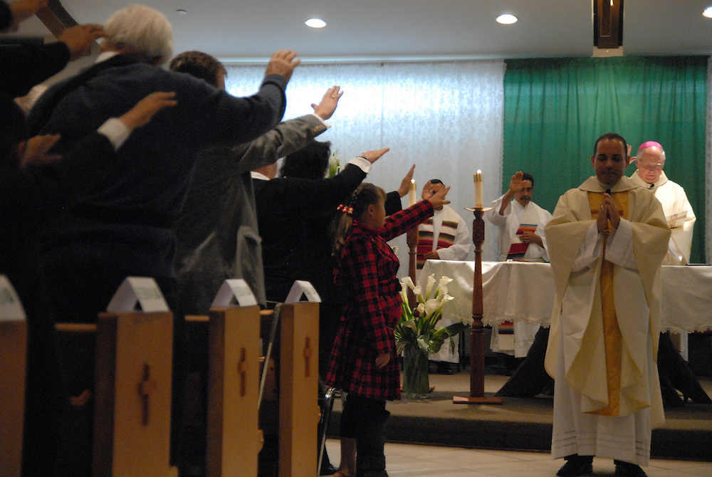 Bishop George Rassas (far right) leads parishioners in prayer while installing Fr. Claudio Diaz (second from right) as Pastor of Mision San Juan Diego in Arlington Heights.