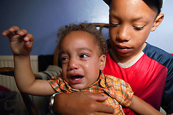 Young boy minding his crying baby brother,