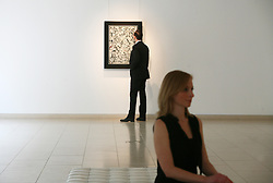 """© Licensed to London News Pictures 10/04/2013.Christie's employees admire some of the world's most famous Abstract Expressionist paintings, including Jackson Pollock's 'Number 19"""" (estimated between £25 - 35 million), that are on display at Christie's in central London and due to go on auction on 15th May in New York. .London, UK.Photo credit: Anna Branthwaite"""