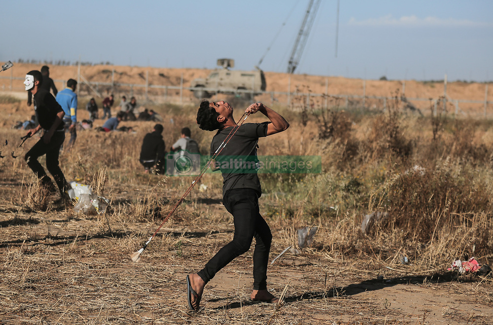 May 3, 2019 - Gaza, gaza, Palestine - A Palestinian protester seen using a slingshot to hurl stones at Israeli troops during clashes..Palestinians clash with the Israeli forces during a protest calling for lifting the Israeli blockade on Gaza and demanding for the right to return to their homeland, at the Israel-Gaza border fence in the southern Gaza Strip. (Credit Image: © Yousef Masoud/SOPA Images via ZUMA Wire)