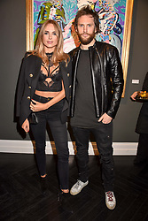 Kimberley Garner and Marc Jacques Burton at a private view of work by Bradley Theodore entitled 'The Second Coming' at the Maddox Gallery, 9 Maddox Street, London England. 19 April 2017.