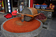 Chili mill inf front of a Chili sales stands grounding chilies into powder, Old Town Muslim quarters, Xian City, Shaanxi, China