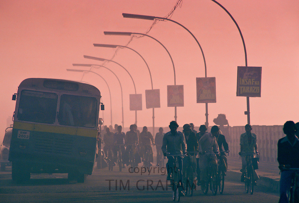 Early morning rush hour in the streets of Delhi, India.  Commuters on bicycles are overtaken by the bus.