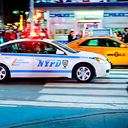NYPD car driving fast in Times Square