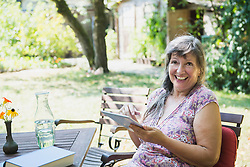 Senior woman with a digital tablet in the garden, Altoetting, Bavaria, Germany