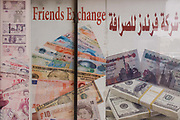 An arabic currency exchange poster in English and Arabic, in the city of Luxor, Nile Valley, Egypt. The detail of the banner shows currencies of many countries including the British Pound showing the queen's head - alongside those of the Egyptian Pound, far right.