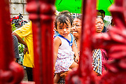 "09 AUGUST 2014 - BANGKOK, THAILAND:      People wait to get into the Ruby Goddess Shrine in the Dusit section of Bangkok for a Ghost Month food distribution. The seventh month of the Chinese Lunar calendar is called ""Ghost Month"" during which ghosts and spirits, including those of the deceased ancestors, come out from the lower realm. It is common for Chinese people to make merit during the month by burning ""hell money"" and presenting food to the ghosts. At Chinese temples in Thailand, it is also customary to give food to the poorer people in the community.    PHOTO BY JACK KURTZ"