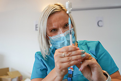 """© Licensed to London News Pictures. 10/07/2021. Sheffield, UK. A health worker prepares to administer  Pfizer/BioNTech vaccine to a member of the public at a pop-up vaccination clinic at Bramall Lane, home to Sheffield United football club in Sheffield, as part of the """"Grab a jab"""" campaign. Photo credit: Ioannis Alexopoulos/LNP"""