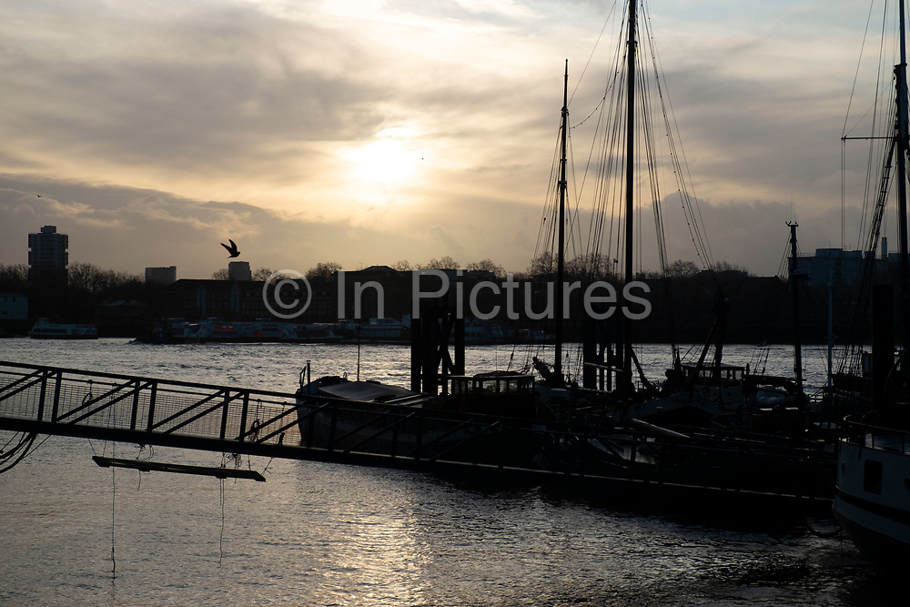 Early morning silhouettes of boats moored at Hermitage Wharf in Wapping on 17th January 2020 in London, United Kingdom. Hermitage Community Moorings HCM is a co-operative which owns and operates the mooring, and is designed to create a small, close-knit community of people committed to boat use and the preservation of historic craft.