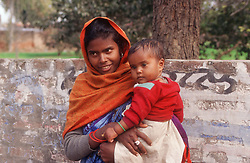 Young woman standing in street holding baby,