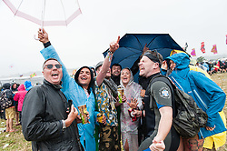 © Licensed to London News Pictures. 26/06/2015. Pilton, UK.  Rain and mud at Glastonbury Festival 2015, with festival goers singing and dancing under their umbrellas and in their waterproof clothes, on Friday Day 3 of the festival.  This years headline acts include Kanye West, The Who and Florence and the Machine, the latter being upgraded in the bill to replace original headline act Foo Fighters.   Photo credit: Richard Isaac/LNP