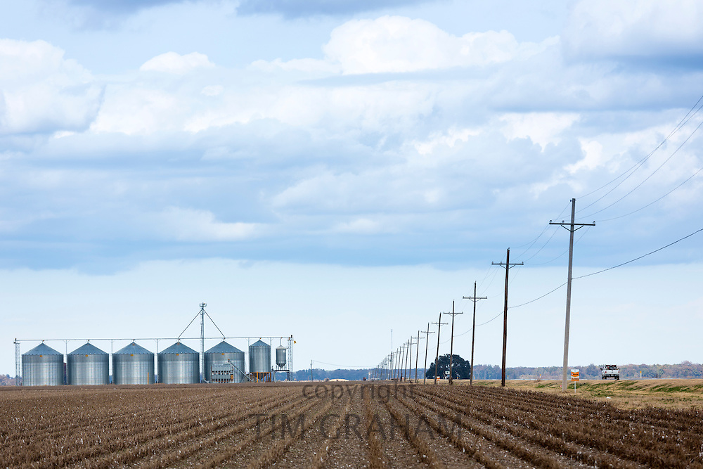 Power lines along Mississippi Delta trail road US Highway 65 and grain silos for crop storage near New Ellton Louisiana, USA