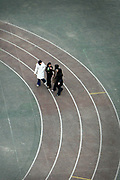 Young girls walk across the running track at St Paul's Way Trust School, Bow, East London. Fewer than 10% of pupils speak English as their first language and 85% are of Bangladeshi origin at the school.