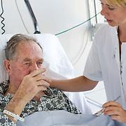 Nederland Rotterdam  31-08-2009 20090831 Foto: David Rozing .Serie over zorgsector, Ikazia Ziekenhuis Rotterdam. Afdeling neurologie, stroke unit, zuster helpt een cva patient met drinken. De patient heeft een beroerte gehad en heeft daardoor oa slikproblemen. Nurse helps old patient to drink, the patient has suffered a stroke. .Na een ernstige beroerte wordt u opgenomen in een gespecialiseerde afdeling of een afdeling intensieve zorgen van het ziekenhuis. Na de eerste 24 uur is het nodig om een aangepast revalidatieprogramma te starten. dat kan bestaan in wisselhoudingen en passieve bewegingen van de verlamde lichaamshelft. Waneer de verlamming niet volledig is, kan onmiddelijk met actieve oefeningen gestart worden. Sommige patiënten zullen ook logopedische behandeling nodig hebben voor spraak- en slikprobleem...Foto: David Rozing ..Holland, The Netherlands, dutch, Pays Bas, Europe, ronde doen, routine verpleegkundigen, op zaal liggen, interactie patient verpleging, praatje maken met, tijd hebben voor, aandacht hebben voor geven, luisterend oor hebben voor ,menselijk contact ,  ,zorgaanbieder, zorgaanbieders, geneeskunde, ill, illness, behandelplan, genezing, genezen, , ziekte bestrijding bestrijden, real people, echte mensen, persoon, personen, oud, oude, op leeftijd, revalidatie, revalideren, revalidation, nursing,ziektekosten,zorgverlener, denkvermogen, cva, zorgverleners,zorgverlening, cognitief, hersenletsel, herseninfarct, ,hersenschade.,braindamage, ,ouderen, bejaard, bejaarde, bejaarden, op leeftijd zijn, probleem met slikken, helpen te met,