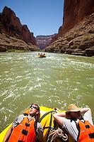Young men taking a nap while rafting the Grand Canyon. Grand Canyon National Park, AZ.