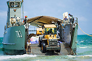 02 AUGUST 2013 - KOH SAMET, RAYONG, THAILAND: A front end loader hauls contaminated trash to a Royal Thai Navy landing craft during the cleanup of an oil spill on Ao Prao beach on Koh Samet island. About 50,000 liters of crude oil poured out of a pipeline in the Gulf of Thailand over the weekend authorities said. The oil made landfall on the white sand beaches of Ao Prao, on Koh Samet, a popular tourist destination in Rayong province about 2.5 hours southeast of Bangkok. Workers from PTT Global, owner of the pipeline, up to 500 Thai military personnel and volunteers are cleaning up the beaches. Tourists staying near the spill, which fouled Ao Prao beach, were evacuated to hotels on the east side of the island, which was not impacted by the spill. Officials have not said when Ao Prao beach would reopen. PTT Global Chemical Pcl is part of state-controlled PTT Pcl, Thailand's biggest energy firm.    PHOTO BY JACK KURTZ