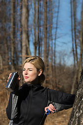 Young woman drinking water after working out in nature
