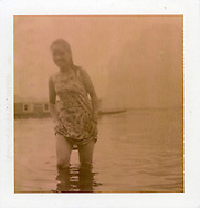 Polaroid chocolate 80 picture of a young woman wading in the water. She must pull her clothes upper to keep them dry. She looks very happy with a great smile on her lips. Guangxi province, China, Asia.
