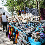 Market stalls selling local souvenirs and handicrafts to tourists visiting Chichen Itza Mayan ruins archeological site in Mexico, with El Castillo in the background.