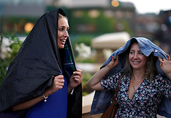 Spectators shelter from the rain under their jackets on day three of the Wimbledon Championships at the All England Lawn Tennis and Croquet Club, Wimbledon.