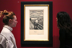 "© Licensed to London News Pictures. 08/04/2019. London, UK. Staff members view Edvard Munch's ""The Scream, 1895"" - which developed from an episode represented in Despair, but with the central figure turned to face the viewer. The swirling reddish-blue clouds are translated in this print into compressed undulating bands of black and white that emphasise the acute panic expressed by the figure. In a twist of fate, Munch's sister Laura was diagnosed in 1894 with schizophrenia and institutionalised in a hospital near the site of The Scream. <br /> <br /> The work of Norwegian artist Edvard Munch (1863-1944) - ""Edvard Munch: love and angst"" at the British Museum opens from 11 April until 21 July 2019. The exhibition focus on Munch's remarkable and experimental prints – an art form which made his name and at which he excelled throughout his life – and will examine his unparalleled ability to depict raw human emotion. It will be the largest exhibition of Munch's prints in the UK for 45 years. Photo credit: Dinendra Haria/LNP"