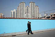 "Pedestrians walk by a walled-in demolished old neighborhood slated for redevelopment in Shanghai, China on 22 December, 2009.  China has tightened land-sale regulations for developers in its latest attempt to take some of the steam out of the potentially overheating property market, this followed a recent vow from Beijing last week to curb what it calls an ""overly fast"" rise in property prices by boosting the supply of cheap public housing and redeveloping slum areas..."