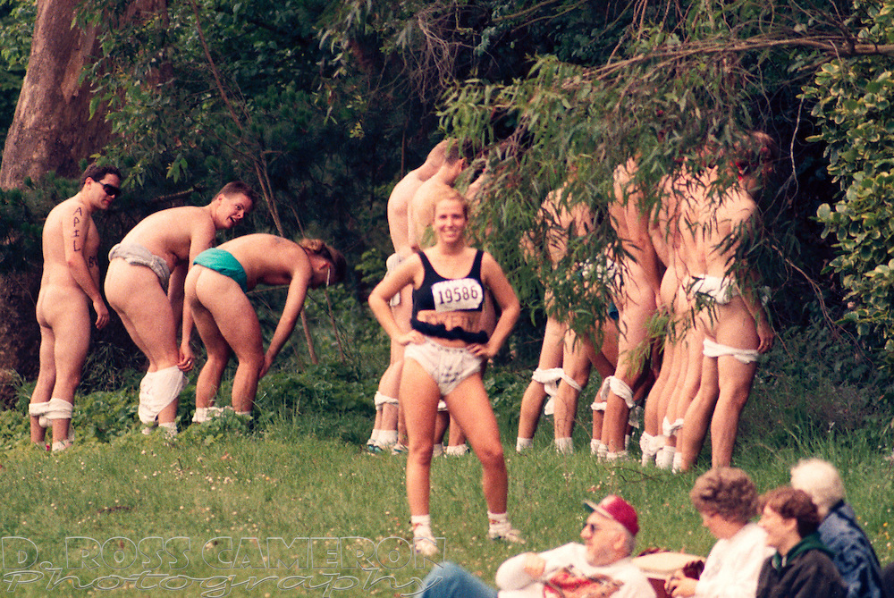 The sole woman member of a centipede from the University of California billing itself as The Bedwetters turns discreetly away while her running mates urinate in the bushes in Golden Gate Park at the 84th running of the Bay to Breakers 12K race, Sunday, May 21, 1995 in San Francisco. (Photo by D. Ross Cameron)